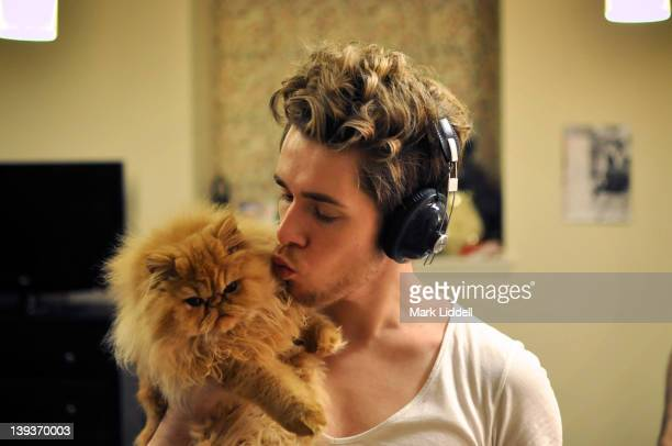 Man wearing headphones holding with cat