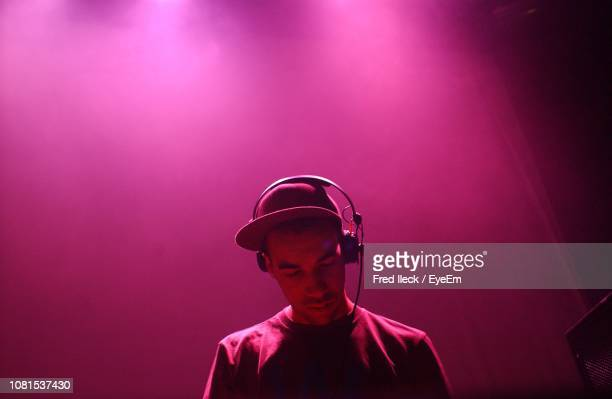 man wearing headphones in illuminated nightclub - dj stock pictures, royalty-free photos & images