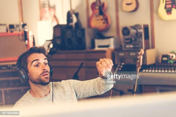 homem usando fones de ouvido no estúdio de gravação de som - compositor - fotografias e filmes do acervo