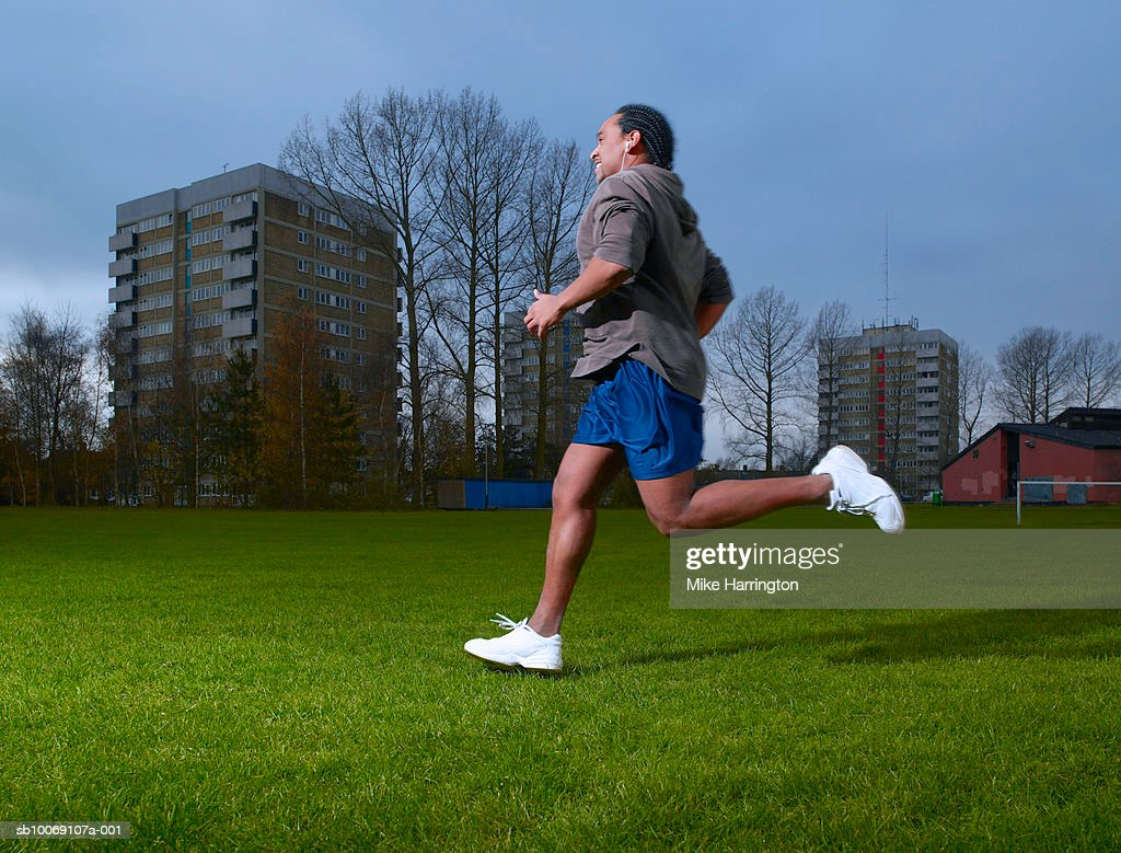 Man wearing headphones, jogging, side view : Stockfoto