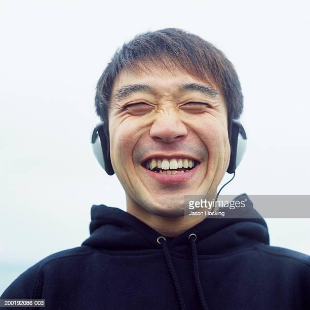 Man wearing headphones, laughing
