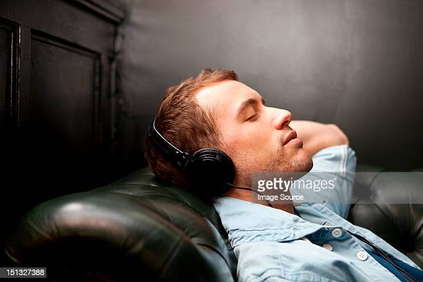 man wearing headphones listening to music - serene people stock pictures, royalty-free photos & images