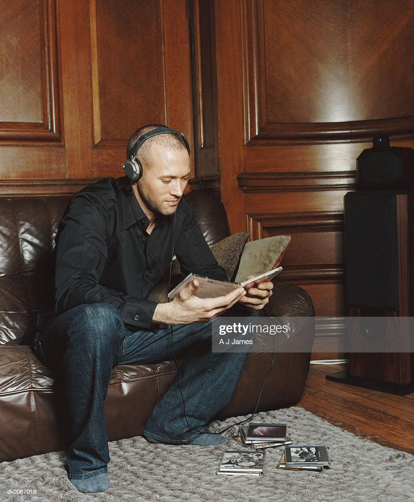 Man Wearing Headphones Looking at Compact Disk Cases : Stock Photo