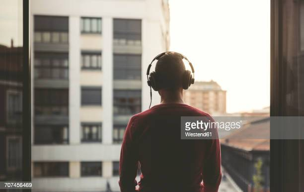Man wearing headphones on a balcony in the city at sunset