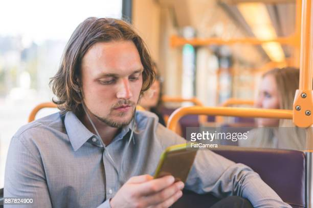 Man Wearing Headphones Rides Public Transportation and Reads His Phone