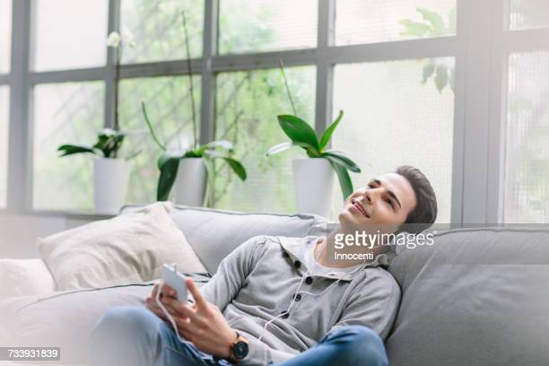 man wearing headphones sitting on sofa - florence douillet photos et images de collection