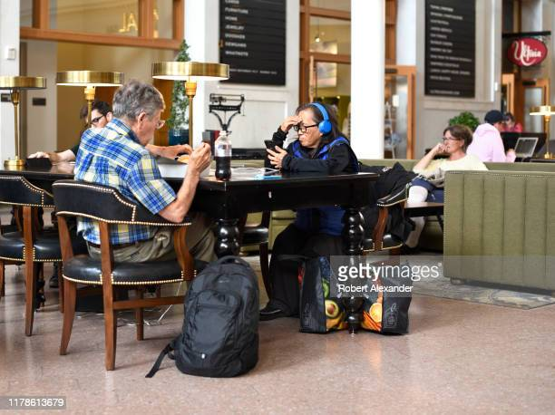 A man wearing headphones uses his smartphone while another man eats lunch in Union Station in downtown Denver Colorado
