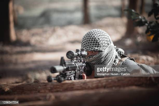 man wearing headscarf aiming rifle on tree trunk in forest - gunman stock pictures, royalty-free photos & images