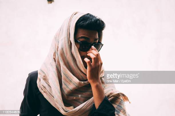 man wearing headscarf and sunglasses standing against wall outdoors - headscarf stock pictures, royalty-free photos & images