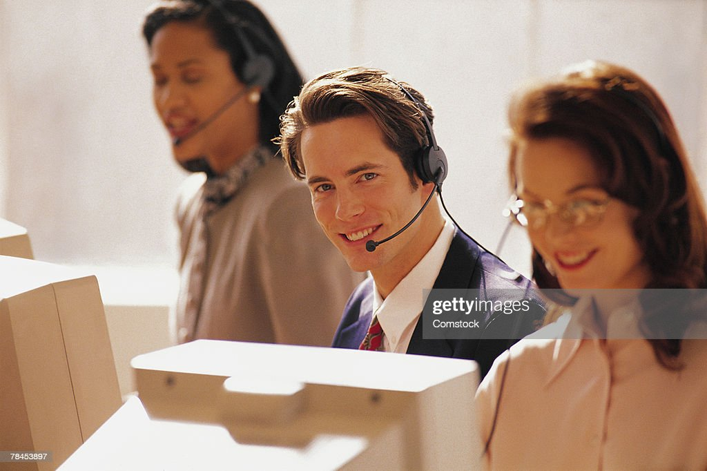 Man wearing headset at computer with others : Foto de stock