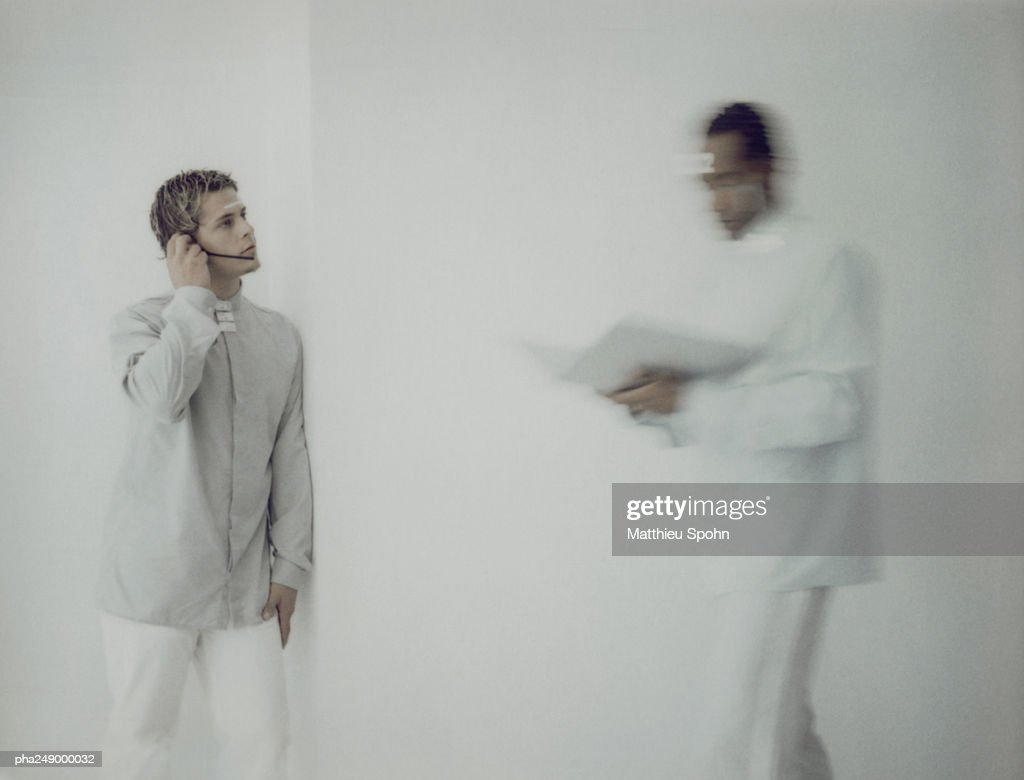 Man wearing headset, other man carrying documents, blurred motion : Stockfoto