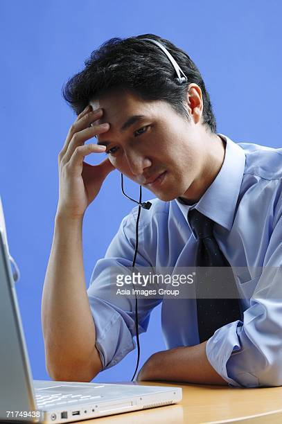 Man wearing headset, using laptop, hand on head