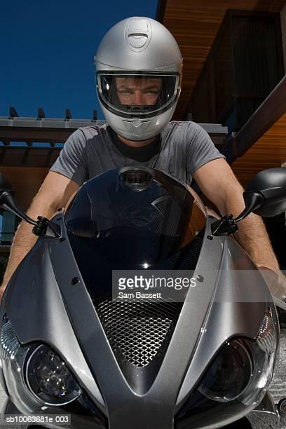 Man wearing helmet sitting on motorbike, portrait