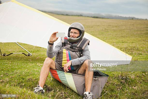man wearing helmet taking selfie, paraglide in background, maui, maui county, hawaii, usa - media_in_honolulu,_hawaii stock pictures, royalty-free photos & images