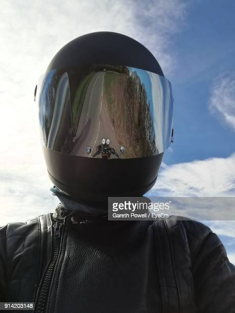 man wearing helmet with reflection of motor cycle against sky - crash helmet stock pictures, royalty-free photos & images
