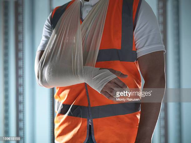 man wearing high visibility jacket with bandaged arm in sling - injured stock pictures, royalty-free photos & images