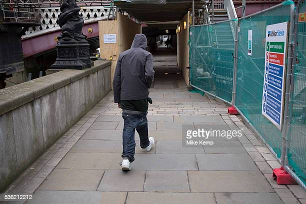 Man wearing his trousers slung low struggles to keep them up London England UK Sagging is a manner of wearing trousers or jeans which sag so that the...