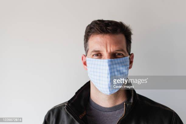 man wearing homemade cloth face mask during covid 19 pandemic. - nose mask stock pictures, royalty-free photos & images