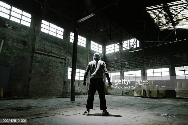 Man wearing hooded jacket, holding football in warehouse, rear view