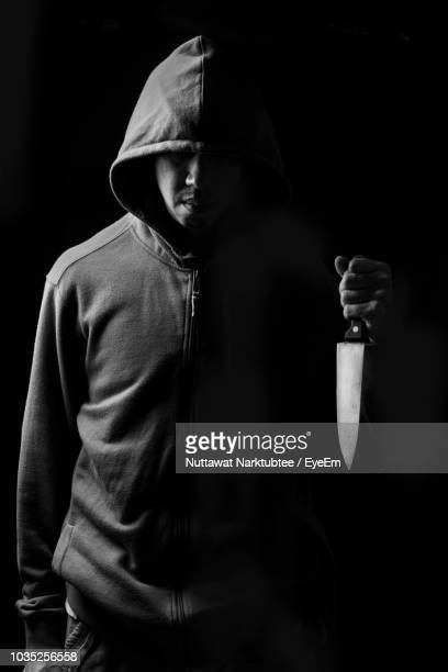 man wearing hooded jacket holding knife while standing against black background - hood clothing stock photos and pictures