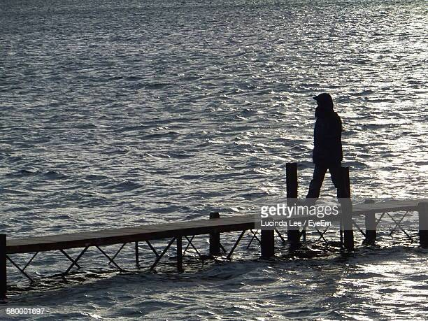 man wearing hooded shirt walking on pier amidst river - lucinda lee stock photos and pictures
