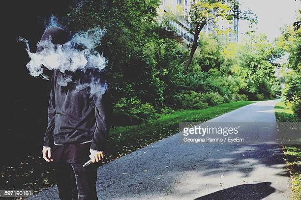 Man Wearing Hooded Shirt With Smoke Standing On Road