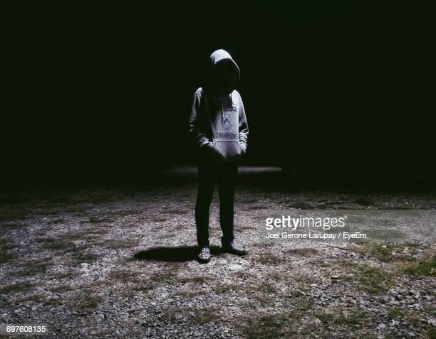 man wearing hooded sweatshirt standing on illuminated ground - capucha fotografías e imágenes de stock