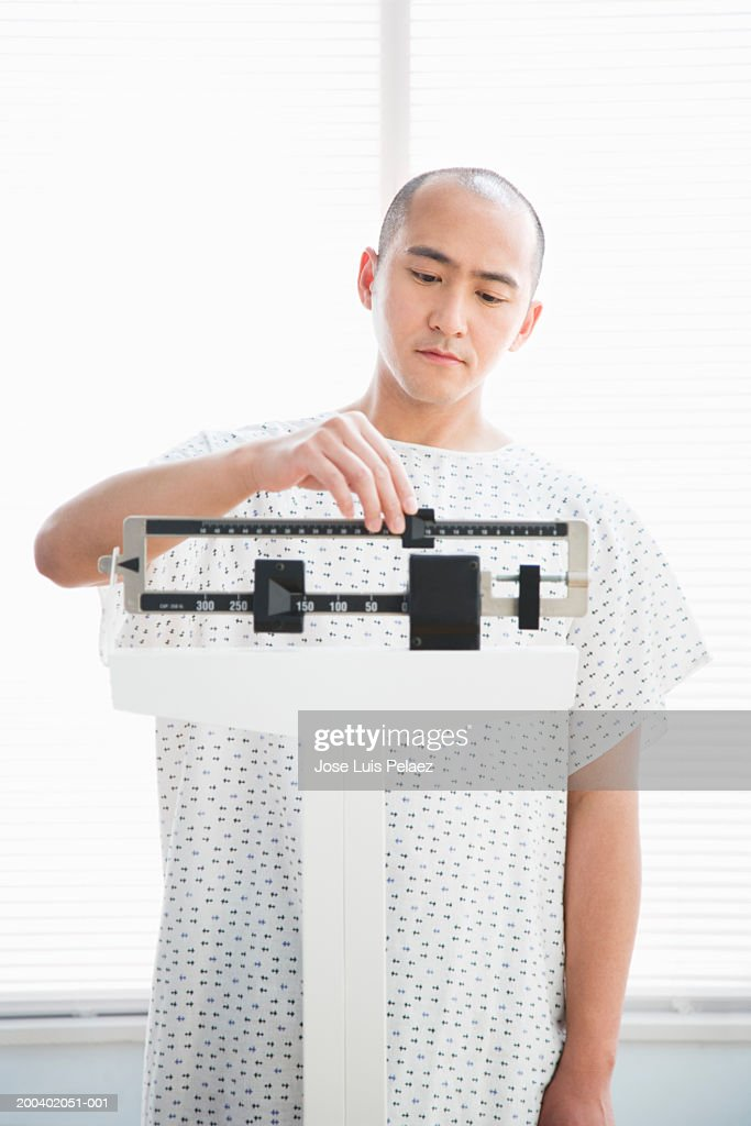Man Wearing Hospital Gown Weighing Himself Stock Photo | Getty Images