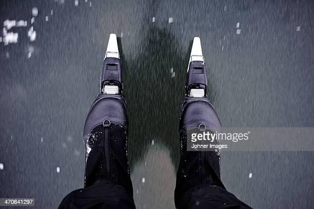 Man wearing ice-skates, low section