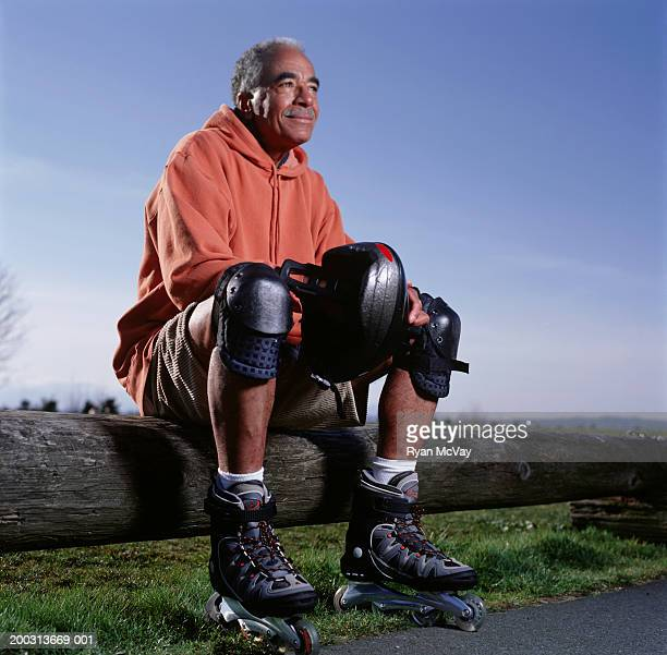 man wearing inline-skates sitting on log fence in park, portrait, low angle view - padding stock pictures, royalty-free photos & images