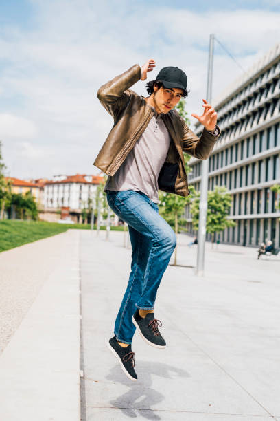 Man wearing jacket and cap jumping on footpath