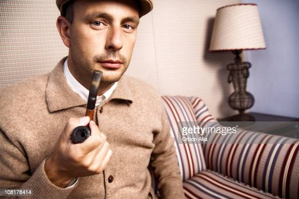 Man Wearing Jacket and Sitting on Couch Holding Pipe