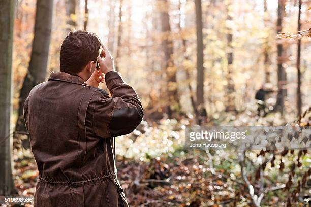 Man wearing jacket standing in forest
