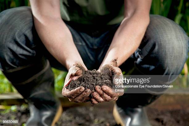 man wearing jeans and boots holding dirt in hands - erdreich stock-fotos und bilder