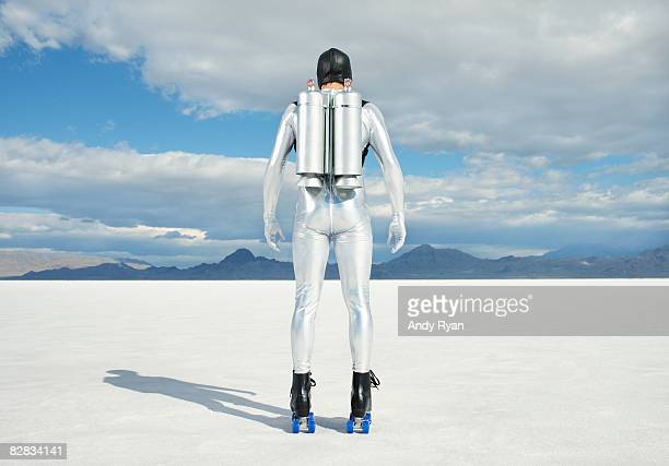 man wearing jet pack and rollerskates on salt flat - space suit stock pictures, royalty-free photos & images