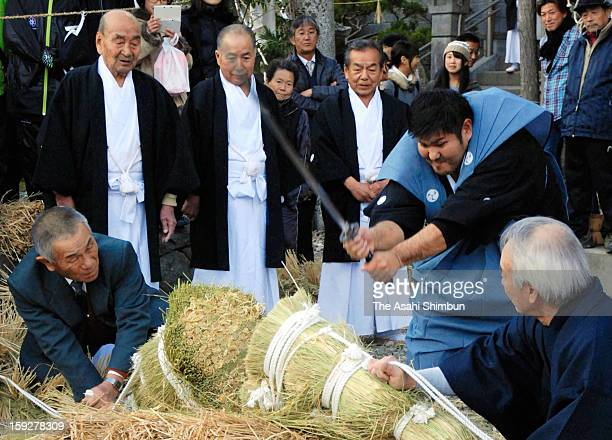 Man wearing Kamishimo, formal wear of Samurai worrior chops Shimenawa sacred rope in hope of good health and good harvest of this year at 'Shime...