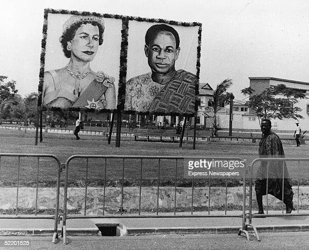 A man wearing Kente cloth walks past a portrait of Ghanaian president Kwame Nkrumah and an unflattering portrait of Queen Elizabeth II erected for...