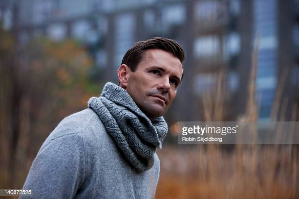 man wearing knitted scarf outdoors - high collar stock pictures, royalty-free photos & images