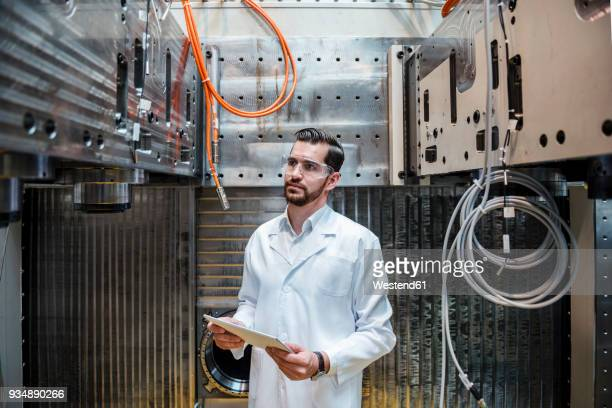 man wearing lab coat and safety goggles at machine holding tablet - laborkittel stock-fotos und bilder