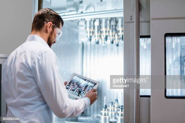 man wearing lab coat and safety goggles at machine in factory looking at tablet - sicherheitsgefühl stock-fotos und bilder