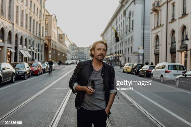 man wearing leather jacket walking in the street, munich, germany - münchen stock-fotos und bilder