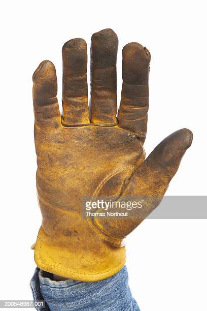 man wearing leather work glove, close-up of hand - work glove stock photos and pictures