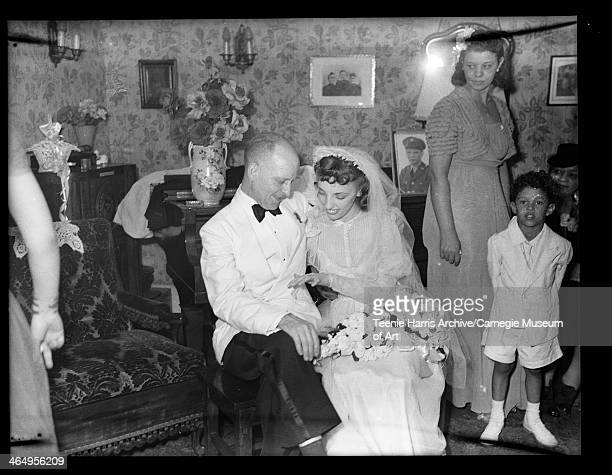 Man wearing light colored dinner jacket and bride Adah Moore Lavelle seated on piano bench in living room with ring bearer Goode in background for...