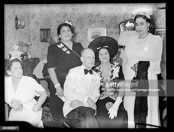 Man wearing light colored dinner jacket and four women including one wearing dark dress with three butterflies posed in living room with ring bearer...