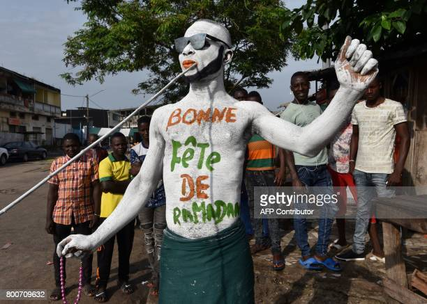 A man wearing makeup reading 'Happy Ramadan' parades through the streets of Abidjan on June 25 as Muslims celebrate the Eid alFitr holiday Muslims...