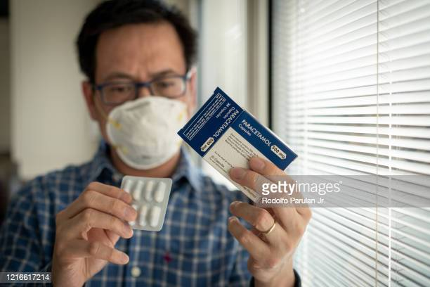 a man wearing mask and holding a box of paracetamol self isolating at home during the coronavirus (covid-19) pandemic - hubei province stock pictures, royalty-free photos & images