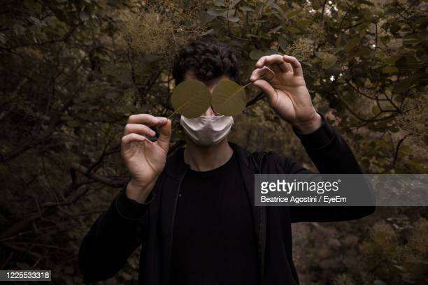 man wearing mask holding leaves while standing against trees - beatrice stock pictures, royalty-free photos & images