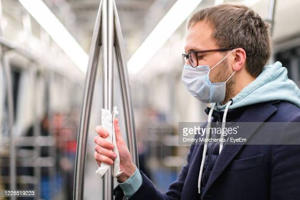 man wearing mask holding pole in train - pole stock pictures, royalty-free photos & images