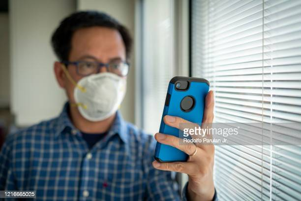 a man wearing mask self isolating at home during the coronavirus (covid-19) pandemic - hubei province stock pictures, royalty-free photos & images
