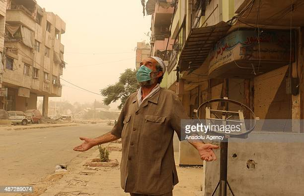A man wearing mask stands on a street during a sand storm in Duma town of Eastern Ghouta Damascus Syria on September 8 2015